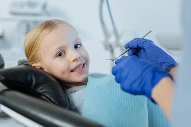 Bambina sveglia che si trova su una sedia del dentista e che sorride mentre ha un controllo della cavità orale condotto da un dentista usando una sonda e uno specchio della bocca