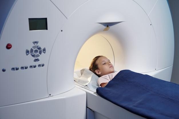 Bambina carina sdraiata su un lungo tavolo prima della procedura di scansione mri