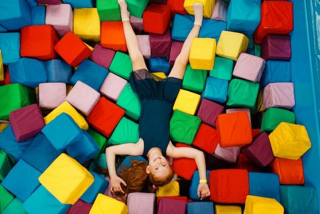 Bambina sveglia che si trova in cubi morbidi, parco giochi