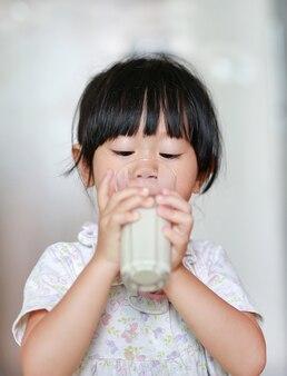 Bambina sveglia in pigiama che beve latte da vetro al coperto al mattino.
