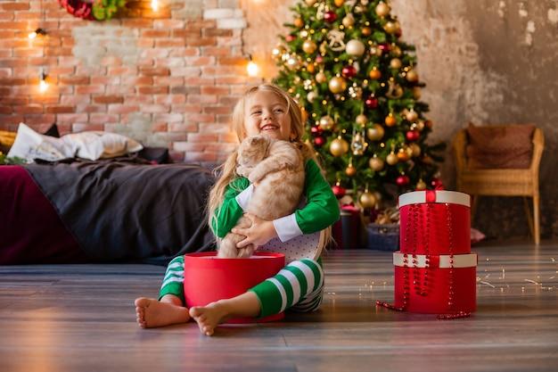 La bambina sveglia in pigiama vicino all'albero di natale tira fuori il gattino della confezione regalo