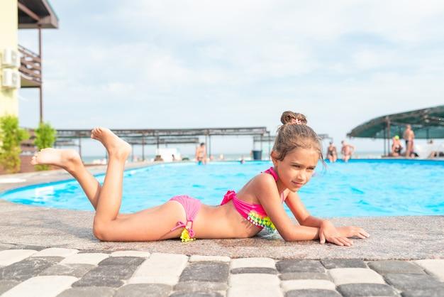 Bambina sveglia in costume da bagno rosa si trova sul bordo della piscina e prende il sole sotto i raggi luminosi del sole