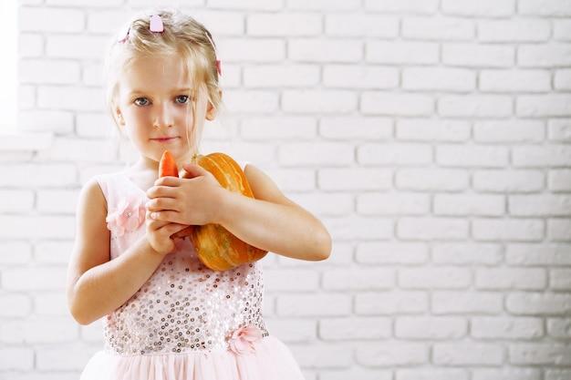 Bambina sveglia in vestito rosa che tiene la zucca nelle sue mani