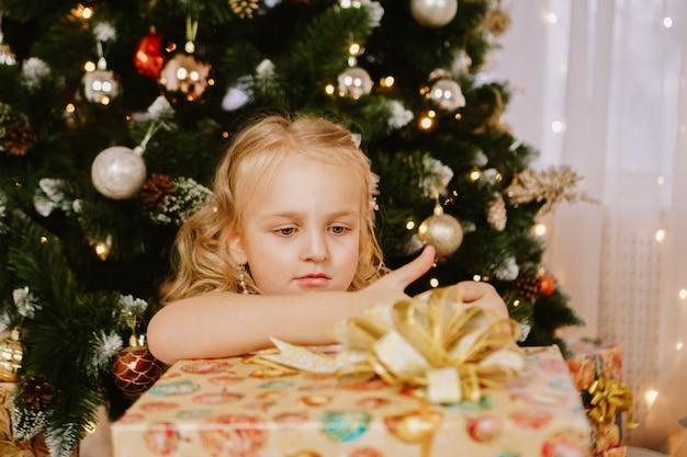 Bambina carina in abito rosa con regalo sullo sfondo dell'albero di natale