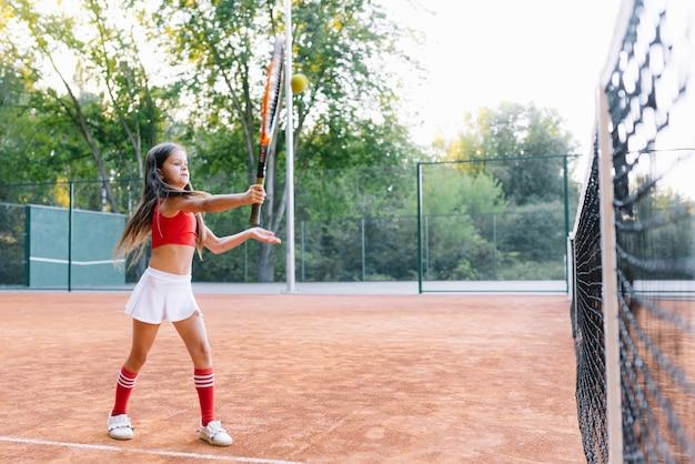 Bambina sveglia che gioca a badminton all'aperto in una giornata estiva calda e soleggiata