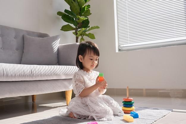 Bambina sveglia che gioca con i mattoni sul pavimento a casa