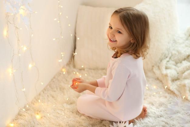 Bambina sveglia che gioca con la ghirlanda a casa