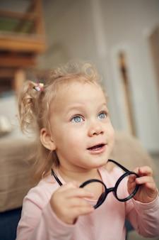 Bambina sveglia che gioca con gli occhiali