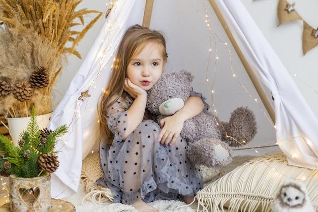 Bambina sveglia che gioca con un orsacchiotto in un wigwam a casa. decorazioni di capodanno.