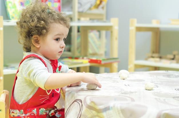 La bambina sveglia gioca, impasta, prepara la pasta per i biscotti.
