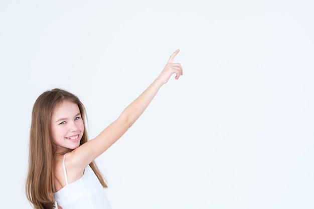 Bambina sveglia che indica qualcosa con una mano e il dito indice sul muro bianco.