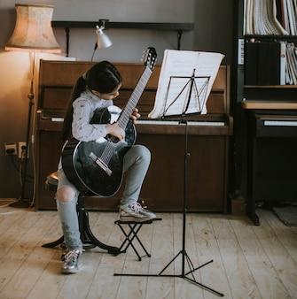 Bambina sveglia che si esercita su una chitarra acustica a casa