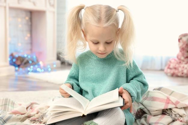 Bambina carina che legge un libro a casa