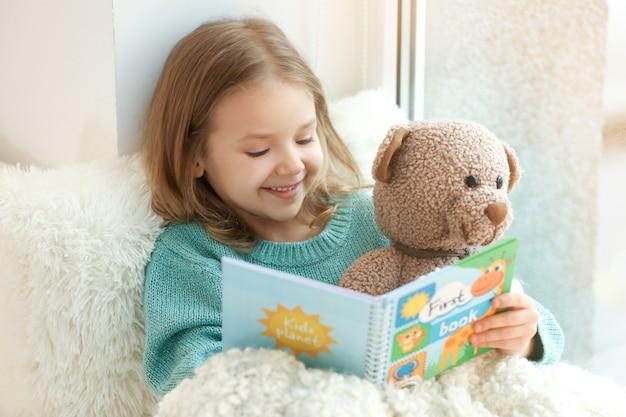 Bambina carina che legge un libro mentre è seduta sul davanzale della finestra a casa