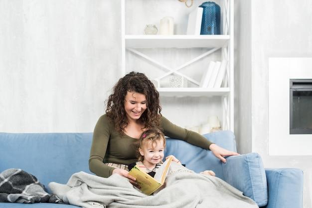 Libro di lettura sveglio della bambina con la madre a casa