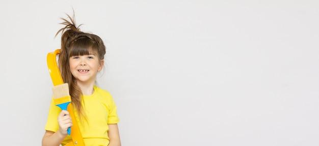 Bambina carina pronta a dipingere il muro con un pennello grande, su sfondo bianco banner spazio copia