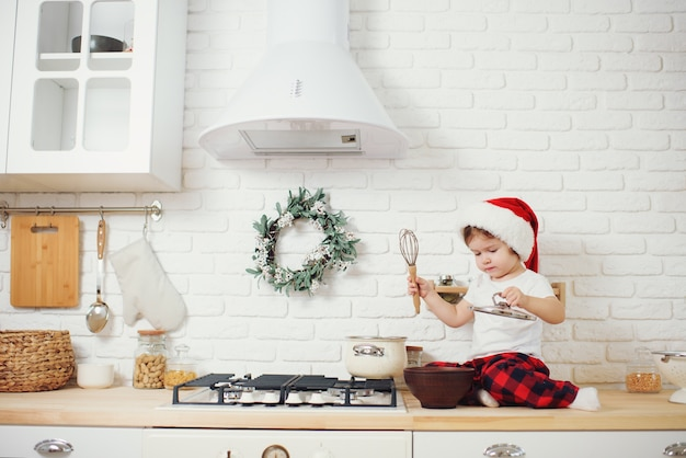 Bambina sveglia in cappello della santa, preparando i biscotti in cucina a casa. si siede sul tavolo della cucina e aiuta la mamma a preparare un festoso pranzo di natale