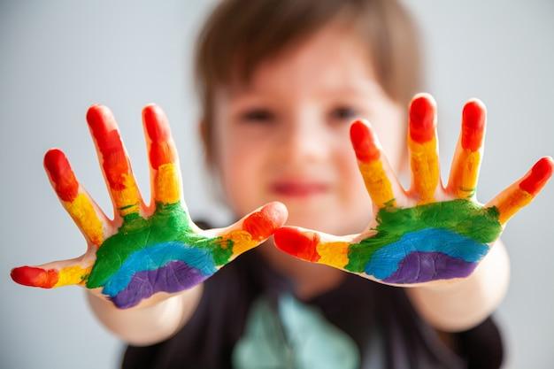 Bambina sveglia che mostra le sue mani con l'arcobaleno dipinto su di loro