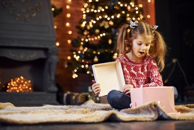 La bambina sveglia si siede nella stanza di natale decorata con scatola regalo.
