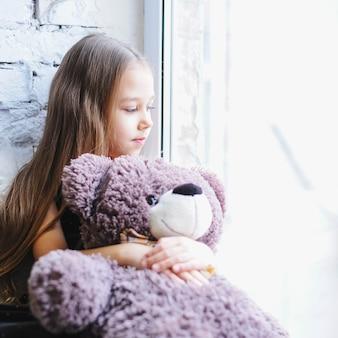Bambina sveglia che si siede vicino alla finestra con il suo orsacchiotto.