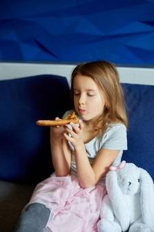 Carina bambina seduta sul divano e mangiare un pezzo di pizza italiana a casa, pasto squisito