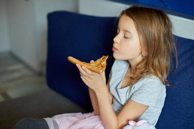 Bambina sveglia che si siede sul divano e mangia un pezzo di pizza italiana a casa