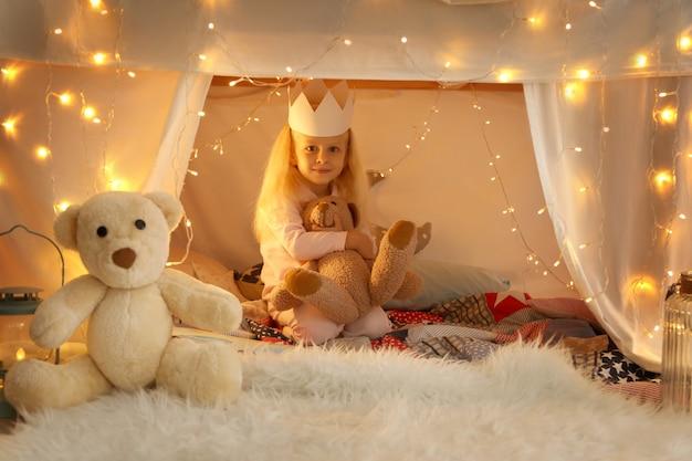 Carina bambina seduta in tugurio con peluche