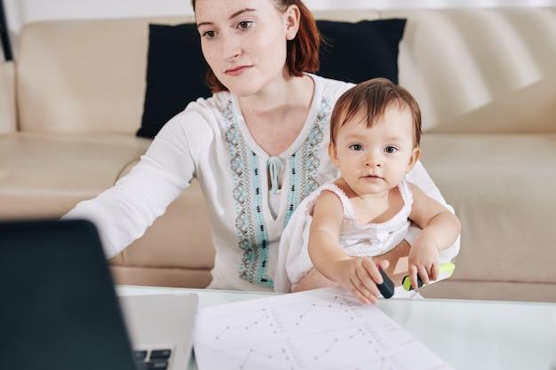 Bambina sveglia che si siede sui giri di sua madre che lavora al computer portatile e controlla i documenti finanziari