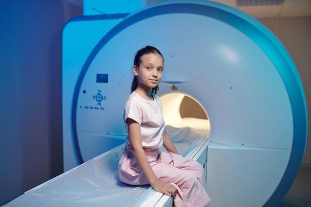Carina bambina seduta sul lungo tavolo della macchina per la risonanza magnetica