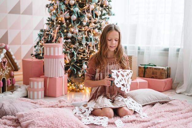 Bambina sveglia che si siede vicino all'albero e che produce fiocchi di neve di carta