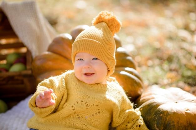 Bambina sveglia che si siede sulla zucca e che gioca nella foresta di autunno