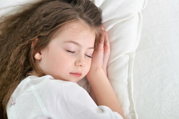 Bambina carina che dorme in un letto