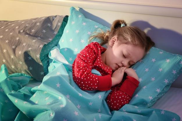 Bambina carina che dorme nel letto