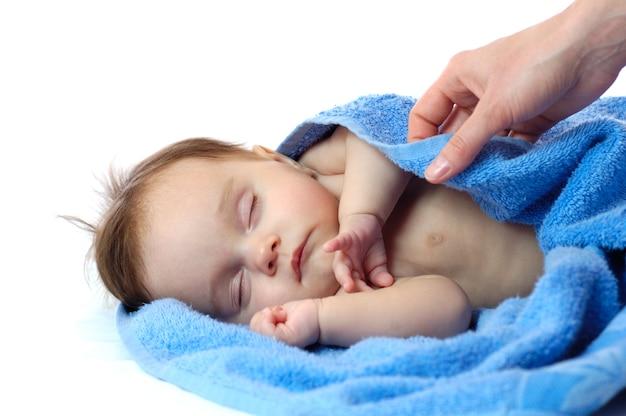 Bambina sveglia che dorme in un asciugamano blu