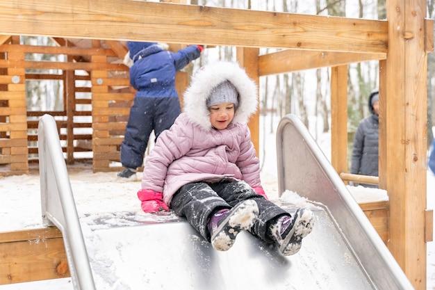 La bambina sveglia scivola giù per lo scivolo durante una passeggiata invernale nel parco giochi