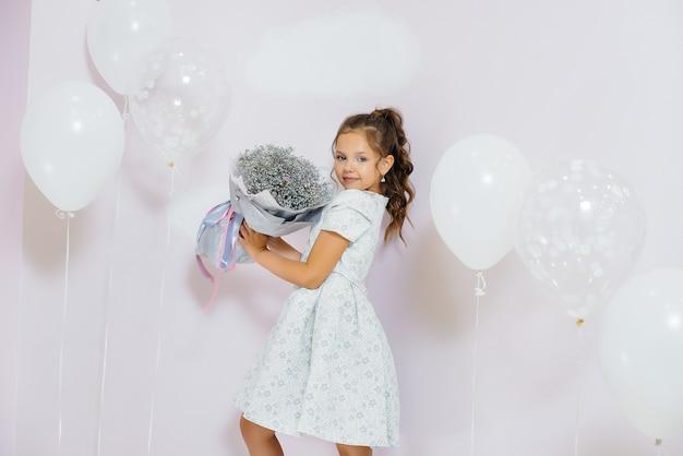 Una bambina carina sorride e posa con un mazzo di fiori
