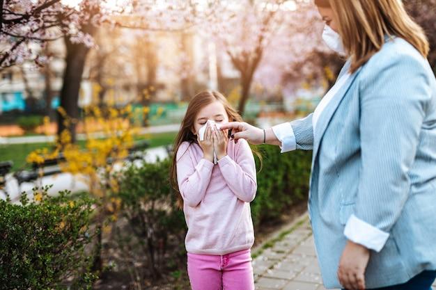 Bambina sveglia che starnutisce nel parco mentre cammina nel parco con sua madre. allergia, influenza, concetto di virus.