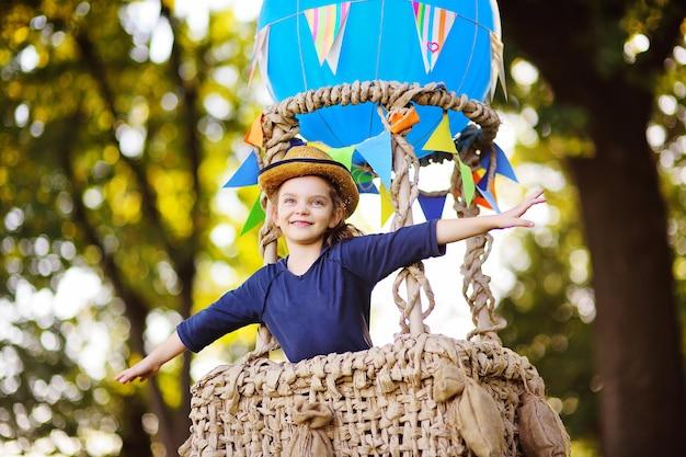 Una bambina carina con un cappello di paglia sorride in un cesto di palloncini. infanzia, avventura