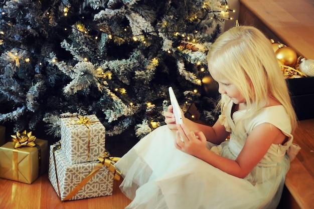 Bambina sveglia che usa la tavoletta digitale mentre è seduta all'albero di natale