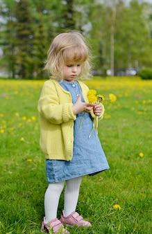 Bambina sveglia che cammina nel parco con i fiori del dente di leone