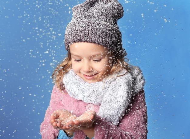 Bambina carina in vestiti caldi che gioca con la neve su uno sfondo colorato