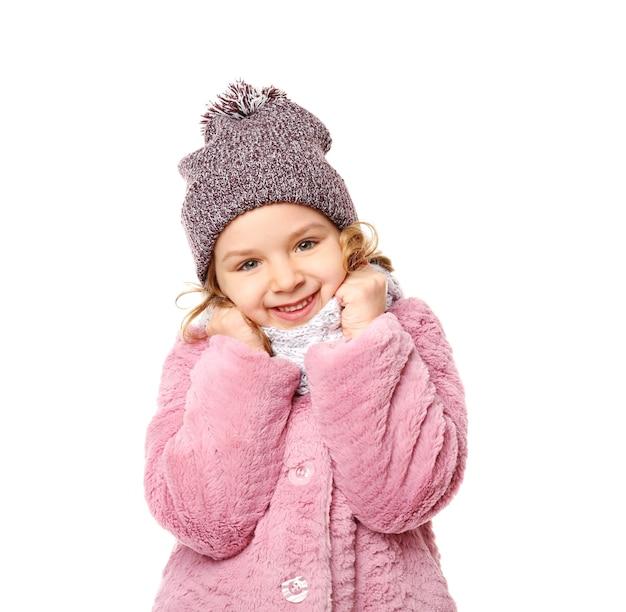 Bambina sveglia in vestiti caldi su fondo bianco
