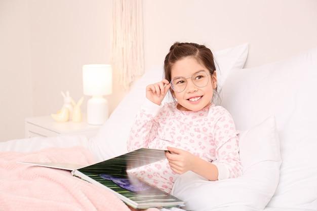 Bambina sveglia con gli occhiali durante la lettura del libro a letto
