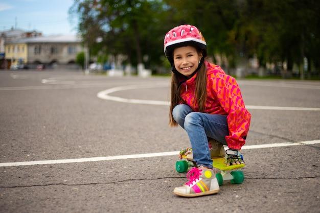 Bambina sveglia che indossa il casco cavalcando uno skateboard nel bellissimo parco estivo