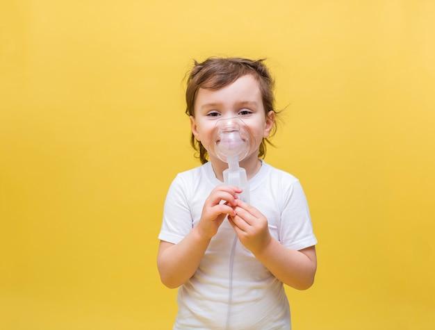 Bambina sveglia in una maglietta bianca su uno spazio giallo. una bambina respira attraverso una maschera. malattie del tratto respiratorio superiore. inalazioni.