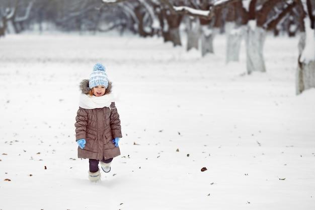 Bambina carina nel parco d'inverno