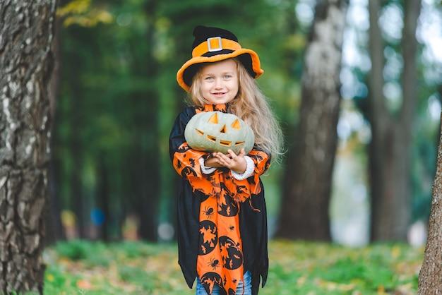 Bambina sveglia in costume da strega per la festa di halloween. tiene una zucca in mano e sta nel parco.