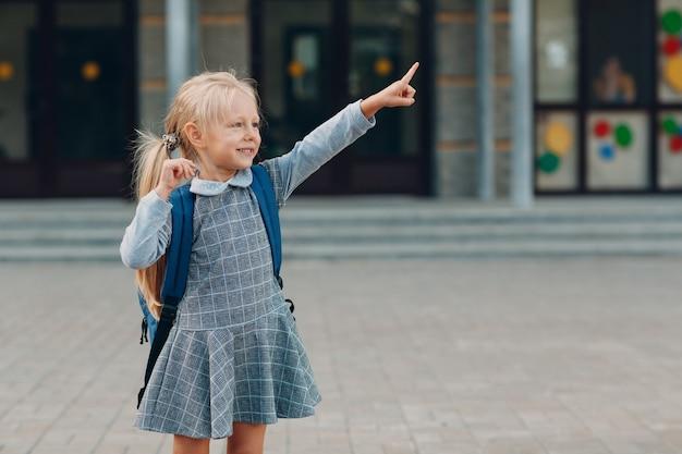 Bambina carina con lo zaino che torna a scuola e indica la strada con il dito