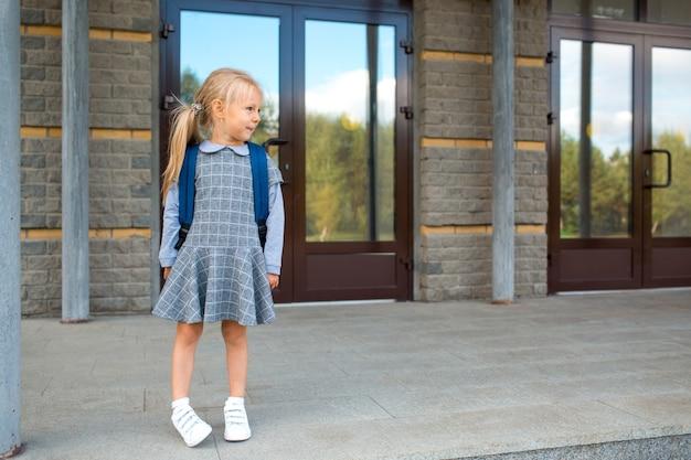 Bambina sveglia con lo zaino che torna a scuola.