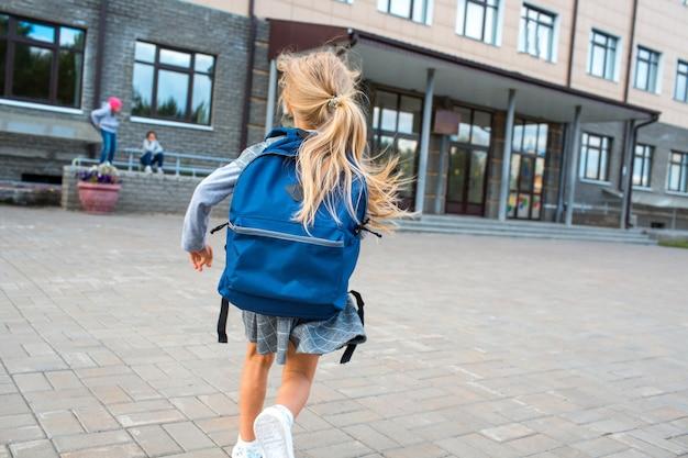 Bambina sveglia con lo zaino che corre di nuovo a scuola.